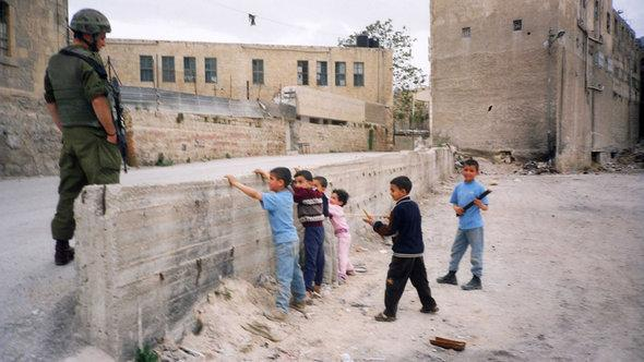 Palestinian children enact a checkpoint control scene in front of an Israeli soldier (photo: © Breaking the Silence)