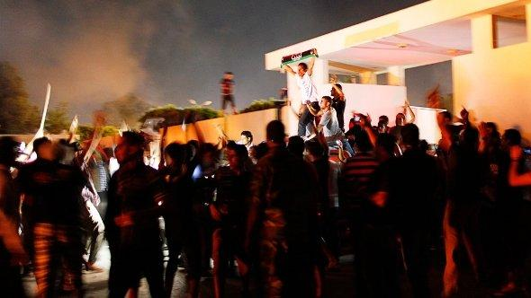 Demonstrators cheer after storming the headquarters of the Islamist Ansar al-Sharia militia group in Benghazi September 21, 2012 (photo: Reuters)