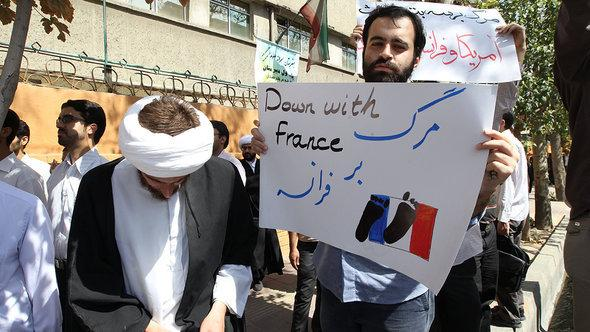 "Pictured: Demonstration in Teheran with a man holding up a placard that reads ""Down with France"" (photo: AFP/Reuters)"