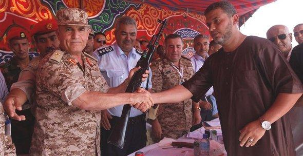 Arms trade-off: Libyan rebells hand over their arms to the Libyan armed forces in September 2012 (photo: Reuters)