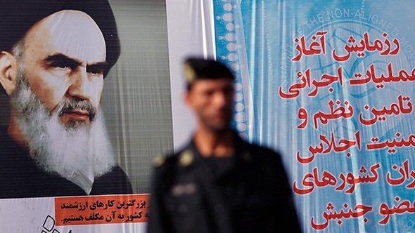 An Iranian policemen and a larger-than-life poster of Ayatollah Khomeini in Tehran (photo: DW)