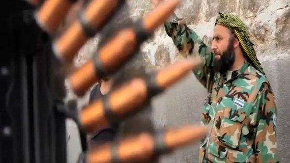 FSA rebel, an ammunition belt in the foreground (photo: AP)