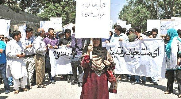 An Afghan woman, holding a placard which reads 'why just women are victims?', marches during a protest against the recent public execution of a young woman for alleged adultery, in Kabul on July 11, 2012. Dozens of Afghan women's rights activists took to the streets July 11 to protest the recent public execution of a young woman for alleged adultery, which was captured in ahorrific video (photo: AFP/Getty Images)