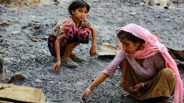 Members of a Muslim Rohingya family gather at the ruins of their home, which was burnt in recent violence, in Mrauk Oo township October 29, 2012 (photo: Reuters)