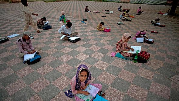 Pakistani children being taught in a public park (photo: AP)