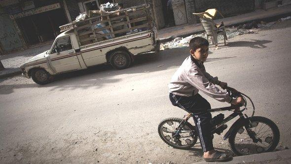 In this Saturday, Oct. 20, 2012 photo, a Syrian boy rides his bike in Karma Jabl district in Aleppo, Syria (photo: Manu Brabo/AP/dapd)