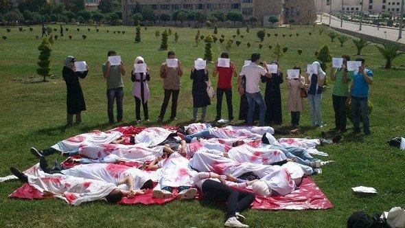 Students lay on the ground to depict a massacre as they take part in an anti-government protest at Aleppo University, June 4, 2012 (photo: Reuters)