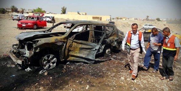 Irakische Rettungskräfte neben den Überresten eines Autobombenanschlags in Kirkuk, September 2012; Foto: EPA/Khalil Al-A'nei/dapd)