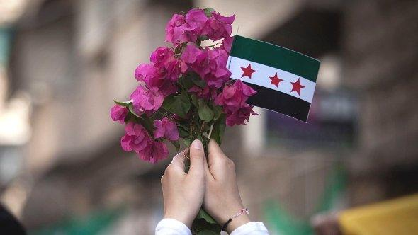 In this Friday, Sept. 21, 2012 photo, a Syrian woman holds a bouquet of flowers and rebel flag during a demonstration in the Bustan al-Qasr neighborhood of Aleppo, Syria. (photo: Manu Brabo/AP/dapd)