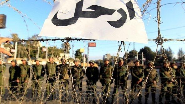 Alt-tag: A sign that reads: 'Leave' is pictured on a barbed wire barricade guarding the presidential palace in Cairo, as Republican Guard soldiers stand in line behind the barricade on 7 December 2012 (photo: Reuters/Mohamed Abd El Ghany)