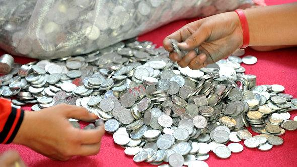 Volunteers count coins collected for Prita Mulyasari (photo: ADEK BERRY/AFP/Getty Images)