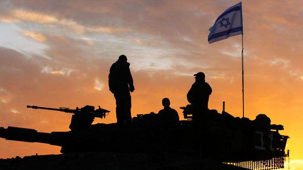 Israeli soldiers prepare to leave their Gaza border position at sunrise on the morning after a ceasefire was agreed between Israel and Gaza's Hamas rulers in November 2012