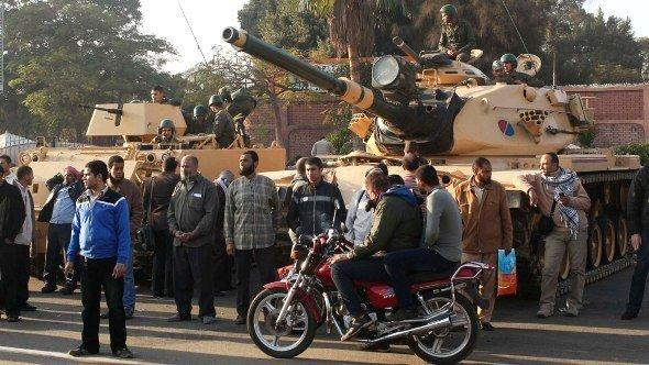 Supporters of the Muslim Brotherhood stand near tanks that were just deployed outside the Egyptian presidential palace in Cairo December 6, 2012 (photo: Reuters)