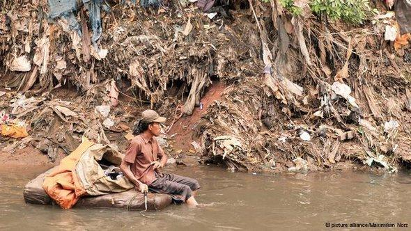 A young man looking for usable waste in the Ciliwung river (photo: dpa)