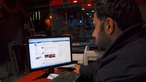 A Syrian man logs on to his Facebook account at an Internet cafe in Damascus (photo: AP Photo/Muzaffar Salman)