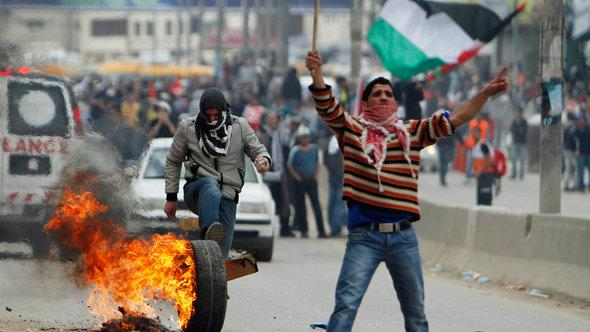 A Palestinian protester rolls a burning tyre down a street during clashes with Israeli security forces at Qalandiya checkpoint near Ramallah (photo: REUTERS/Mohamad Torokman)