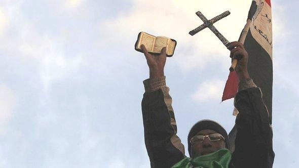 An anti-Mursi protester holds the Koran, a Cross and the Egyptian national flag on top of a wall in front of the presidential palace in Cairo, December 2012 (photo: Reuters/Amr Abdallah Dalsh)