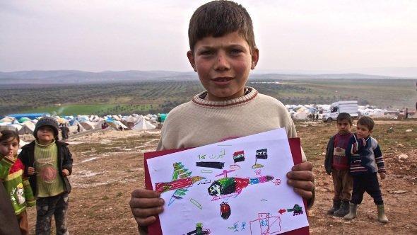 A Syrian boy, Abdullah, 9, from Hama depicts a helicopter dropping a barrel bomb of TNT on his home, a popular weapon in the regimes arsenal. Atmeh refugee camp, Syria, 18 January 2013 (photo: Andreas Stahl/DW)