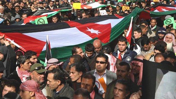 Protesters from the Islamic Action Front and other opposition parties hold up Jordanian national flags during a protest in Amman, 18 January 2013 (photo: Reuters/Majed Jaber)