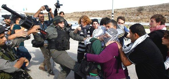 Israeli border police scuffle with Palestinian and international activists as they block a road used by Israeli settlers near the West Bank village of Shuqba (photo: Reuters)