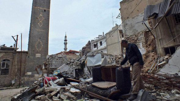 A man inspects rubble in Homs, March 2013 (photo: Reuters)