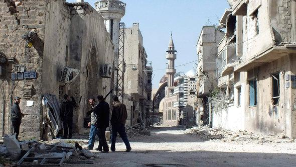 Free Syrian Army fighters inspect damage in the besieged area of Homs, March 2013 (photo: Reuters)