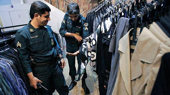 Police officers examine items of clothing in a boutique in Tehran (photo: ISNA)