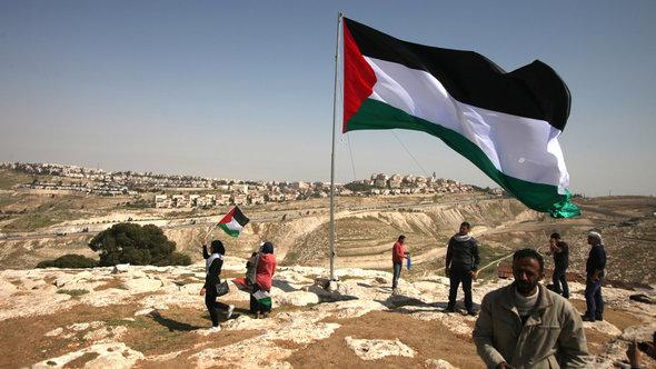 Palestinians hoist a huge Palestinian flag close to Israel's largest Jewish settlement of Maale Adumin on the outskirts of Jerusalem ahead of Obama's visit (photo: AFP/Getty Images)