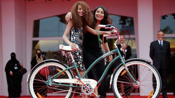 "Haifaa al-Mansour and Waad Mohammed pose with the bicycle from the film on the red carpet during the premiere screening of ""Wadjda"" during the Venice Film Festival 2012 (photo: Reuters)"