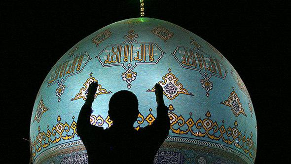 An imam prays in front of the main mosque in the Iranian city of Qom (photo: AFP/Getty Images)