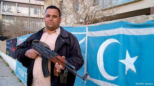 A man standing with a rifle in front of the turquoise flag used by Iraqi Turkmen (photo: DW/K. Zurutuza)
