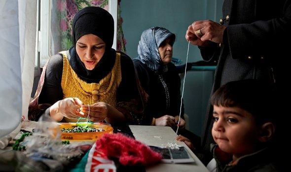 Syrerin aus Aleppo arbeitet an einer Nähmaschine; Foto: Victor Breiner