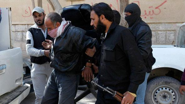 Members of the Islamist Syrian rebel group Jabhat al-Nusra holding a detainee, March 2013 (photo: Reuters)