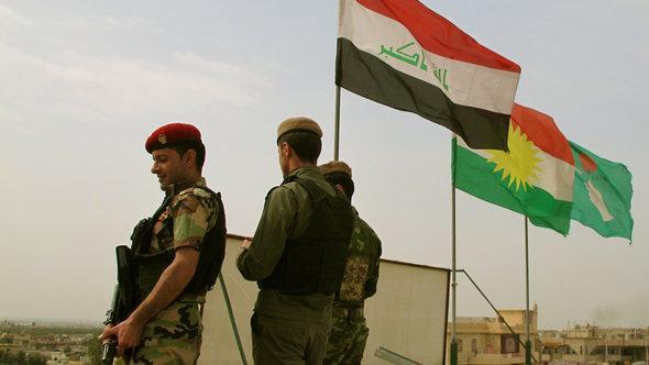 Iraqi and Kurdish flags on display over Bashiqa (photo: DW/Karlos Zurutuza)