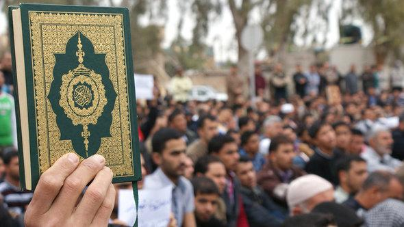 A man holds up a copy of the Koran in Buquba, north of Iraq, during a political demonstration in 2013 (photo: Reuters)