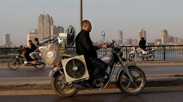 Man on a motorcyle in Cairo, transporting an array of electric fans (photo: AP)