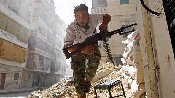A Free Syrian Army fighter takes cover during clashes with Syrian Army in the Salaheddine neighbourhood of central Aleppo (photo: Reuters)