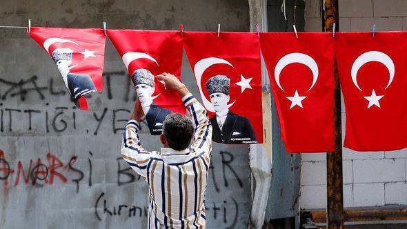 متظاهر يُعَلِّق العلم التركي مع صورة أتاتورك في الشارع. رويترز