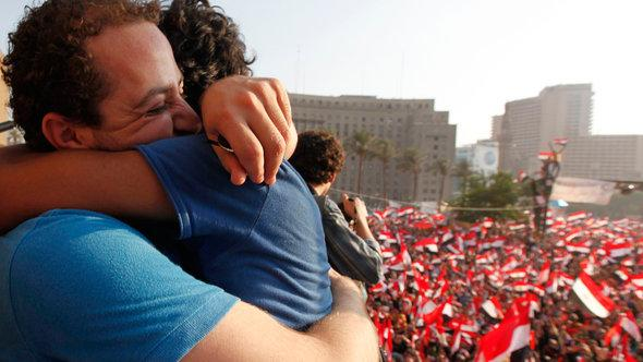 Two demonstrators hug during a protest against Egyptian President Mohamed Mursi in Tahrir Square in Cairo, 3 July, 2013 (photo: Reuters)