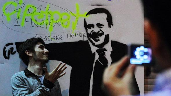 Activist in front of an Erdogan graffito in Istanbul (photo: Gaia Anderson)