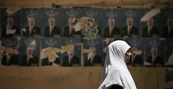 An Egyptian woman walks past election posters in Egypt (photo: AP)
