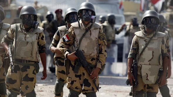 Army soldiers wear gas masks before clashes with members of the Muslim Brotherhood and supporters of deposed Egyptian President Mohamed Morsi at Republican Guard headquarters in Nasr City, a suburb of Cairo July 8, 2013 (photo: Reuters)