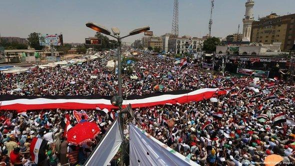 Egyptian supporters of the Muslim Brotherhood and deposed president Mohamed Morsi deploy a giant national flag during a rally outside Cairo's Rabaa al-Adawiya mosque on July 12, 2013, following Friday noon prayer (photo: AFP/Getty Images)