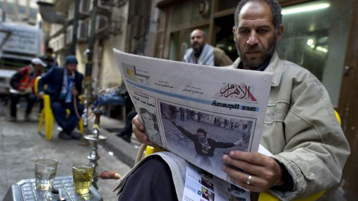 An Egyptian man reads a newspaper while enjoying some tea (photo: AFP/Getty Images)