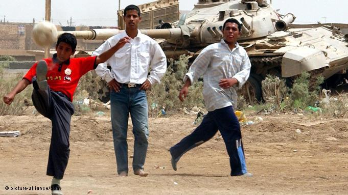 Young Iraqis playing football near an abandoned, damaged tank of the Iraqi army in Baghdad, Thursday, 15 May 2003 (photo: picture-alliance/dpa)