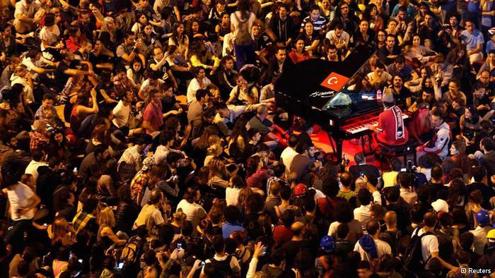 Davide Martello playing his piano in Taksim Square surrounded by crowds of protesters (photo: Reuters)