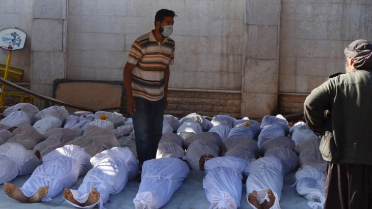Syrian activists inspect the corpses of civilians killed by nerve gas in north-eastern Damascus (photo: Reuters)