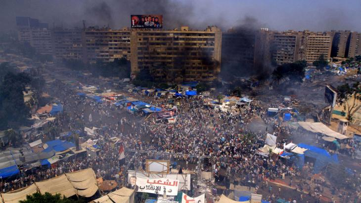 Smoke rises at Rabaa al-Adawya square following clashes between Egyptians supporting ousted president Morsi and riot police in Cairo, Egypt, 14 August 2013. Violence spread across much of Egypt after police cleared two encampments of Morsi's supporters, showering protesters with tear gas as the sound of gunfire rang out (photo: Ahmed Asad/APA/Landov)