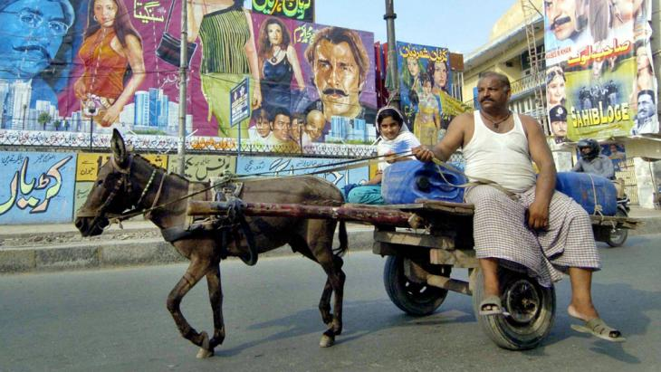 A Pakistani man rides on a donkey cart past film advertisements in Lahore (photo: AFP/Getty Images)