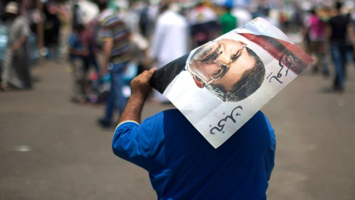 An Egyptian supporter of the Muslim Brotherhood walks holding a poster featuring deposed president Mohamed Morsi during a rally to support him on July 6, 2013 outside Cairo's Rabaa al-Adawiya mosque (photo: credit should read Mahmud Hams/AFP/Getty Images)